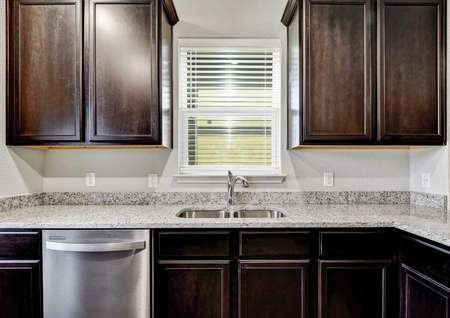 Jasper kitchen designed with granite counters, brown wooden cabinetry, and stainless steel dishwasher