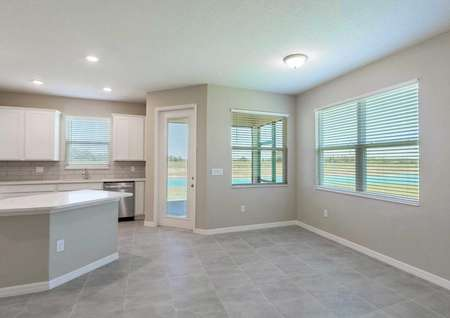 The dining and kitchen area in the Tuscany floor plan that has tile flooring, multiple windows and ceiling light.