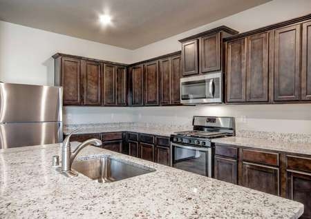 Snowflake kitchen with granite countertops, brown cabinetry, and recessed light