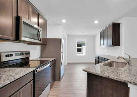 Close up of spacious kitchen with stainless steel appliances and a breakfast nook.