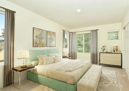 staged bedroom with 4 windows, queen bed greenish blue fabric, 2 nightstands with lamps, bench, rug, cabinet, drapes