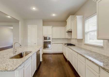 Fairview home plan finished kitchen with light color granite counters, undermount stainless steel sink, and beautiful white cabinets