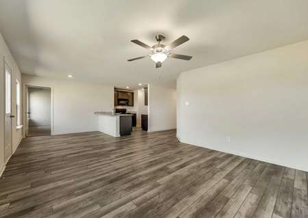 Rio Grande great room with ceiling fan, wood flooring, and white on off white wall paint