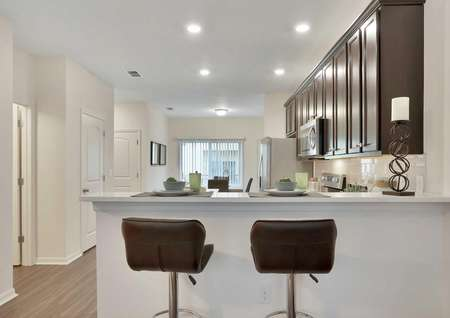 Pine model home kitchen area with two brown-backed barstools, a candle, and place settings on the granite countertop