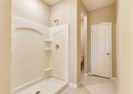 Bathroom with tile floors, a toilet that has a closed-door beside it and a walk-in shower in the Wekiva floor plan.