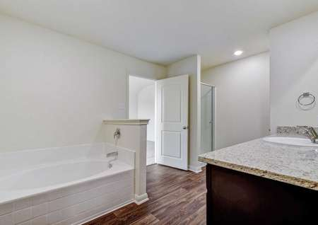 Rio bathroom with canned light fixtures, granite countertops, and brown cabinetry