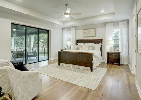 Staged master bedroom with tall ceilings, white walls, light wood flooring and back yard views.