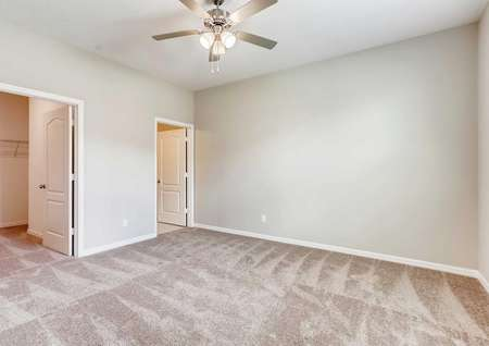 The master bedroom in the Mateo model. Light tan walls, tan carpeting, white baseboards and a walk-in closet