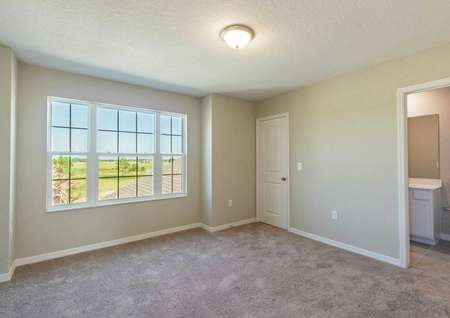 A bedroom in the Calabria floor plan that has carpet floors, ceiling light and a doorway to the rooms bathroom.