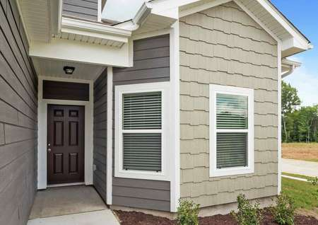 Closeup picture of the Cypress home's exterior light grey siding with white trim and brown door with patio lighting and landscaped yard