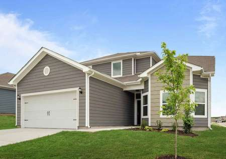 A view of the Cypress model home from the landscaped front yard showing the white 2 car garage white trim and grey siding