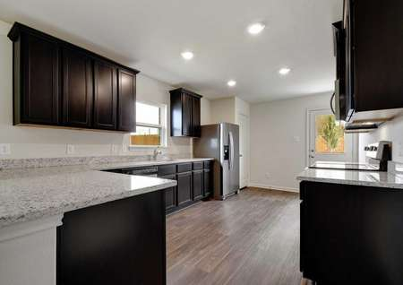 Medina kitchen with recessed lights, dark custom cabinetry, and light colored granite counters