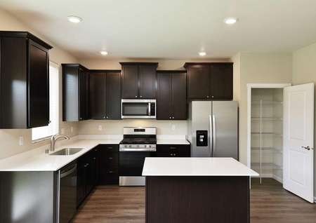 The Northwest Cypress kitchen offers another view showing an open pantry door and stainless steel appliances.