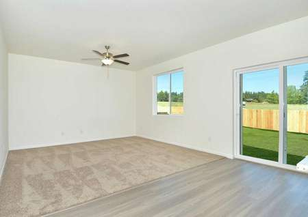 Cypress great room with carpet in the family room, wood style flooring in the dining area, and white sliding patio door