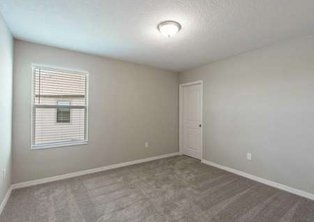 A secondary bedroom upstairs in the Tuscany floor plan has brown carpet, tan walls and a window with covered blinds.