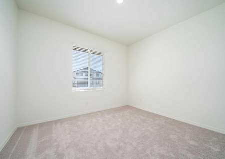 Balboa bedroom with recessed light, white trim and walls, and soft brown carpeting
