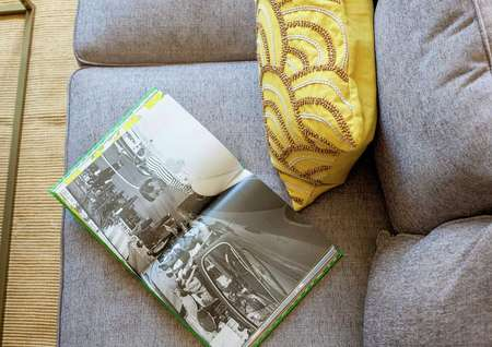 Staged living room with grey sofa, yellow throw pillow with brown pattern, and open book with black and white picture on it