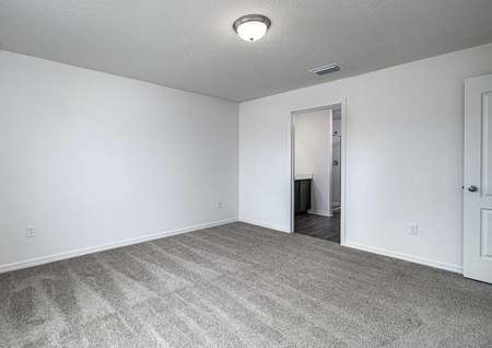 Sizable master bedroom with carpeted floors leading to its own full bathroom.