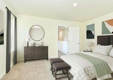 staged master bedroom with king bed, nightstand with lamp, 2 benches, dresser, round mirror, art, window gray drapes