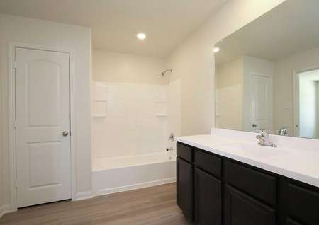 Trinity bathroom with white bathtub and sink, large vanity mirror, and brown cabinets