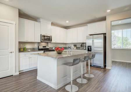 Fully furnished kitchen with whitecabinets, granite countertops and breakfast barin the Loomis floor plan.