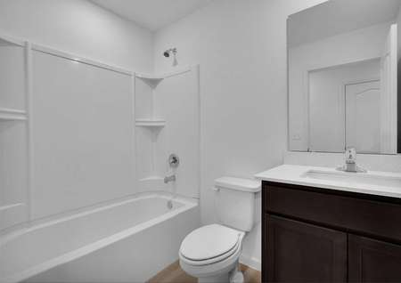 A bathroom in the St. Martin floor plan with a bathtub/shower combo, dark brown cabinets and quartz countertops.