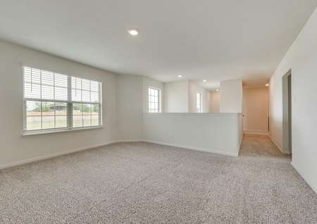 The upstairs area of this home has a game room with brown carpet and white walls.