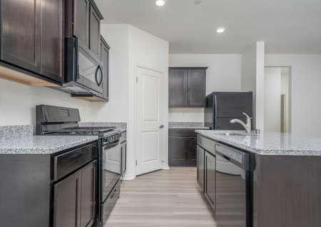 Balboa kitchen with recessed lights, black appliances, and brown cabinetry