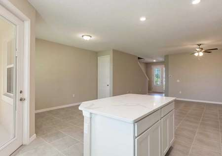 The kitchen island in the Calabria floor plan with quartz countertops, white cabinets and a tile flooring all around it.