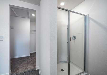 Step-in shower and adjacent walk-in closet with plenty of storage space.