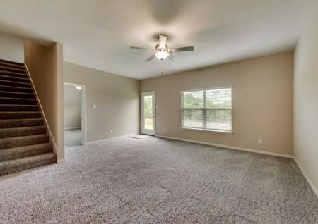 Family room with tan walls, brown carpet, ceiling fan and back yard views.