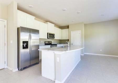 A kitchen island in the St. Johns floor plan with a sink, granite countertops and tile flooring around it.