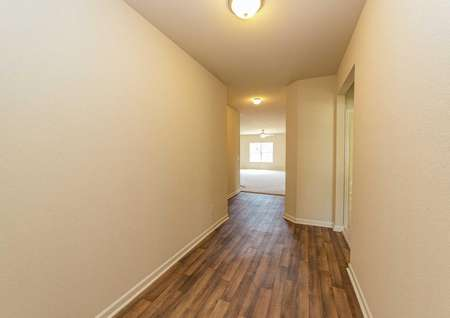 Hardwood flooring in the hallway leading to the living room of the Allatoona model plan