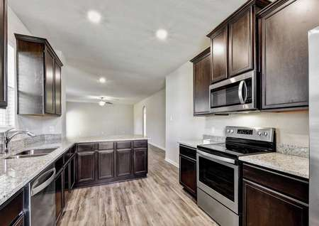 Jasper completed kitchen with wood flooring, granite countertops, and stainless steel appliances