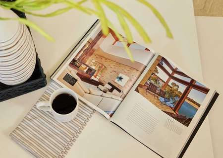 Staged image of coffee table with open book, plant vase, and cup of coffee.