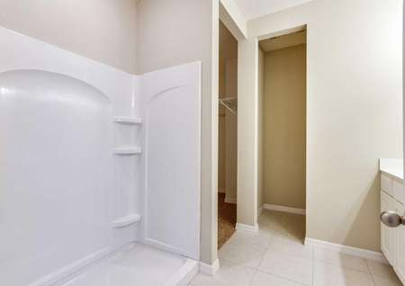 The Mykka floor plans bathroom has a walk-in shower, tan walls, white baseboards and tile flooring.