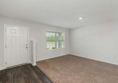 Hartford home entryway with carpet family room, white front door, and recess lights
