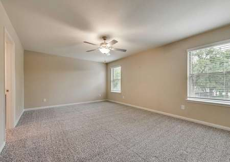 Ozark master bedroom with ceiling fan, carpeted flooring, and access to master bath