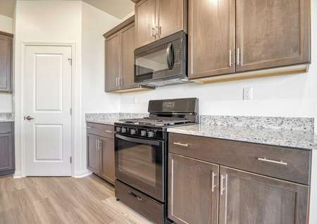 The kitchen in the Rosebud floor plan with brown cabinets, a gas range stove, granite countertops and a pantry.