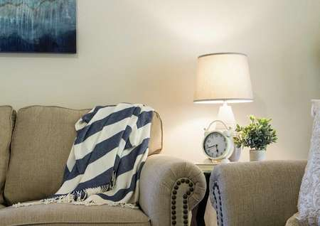 Staged home with light brown colored modern sofa, white and blue blanket and painting hanging on the wall.