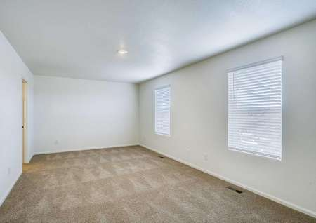 Mesa Verde bedroom with two large windows, overhead light, and soft brown carpet