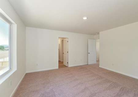 Spacious upstairs master bedroom with carpet and large window and attached bathroom.