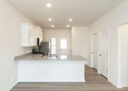 View into kitchen with white cabinets, granite counters, stainless appliances, recessed light and plank flooring.