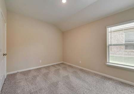A secondary bedroom in the Texoma floor plan with tan walls, white baseboards and light-brown carpet flooring.