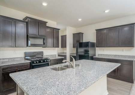 The Del Mar floor plan's kitchen with an island, modern wood cabinets, recessed lighting and wood-like flooring.