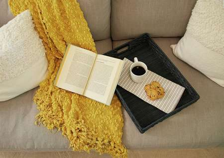 Staged living room with book, coffee cup, and yellow shawl on couch.