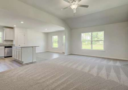 Open living room with carpet, window to backyard, ceiling fan looks into kitchen with island and breakfast room.