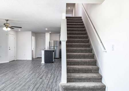 Entertainment space adjacent to carpeted stairs leading to multiple bedrooms.