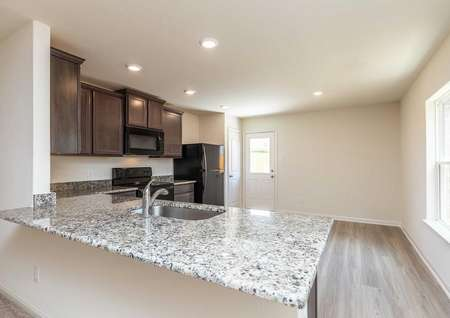 Pecan kitchen with recessed lights, light color granite counter, and dark wooden cabinets