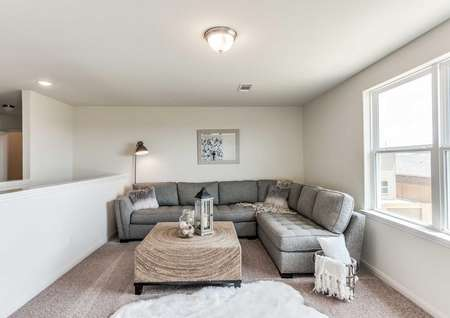 Driftwood staged loft in model with grey sectional sofa, white throw rug, and wooden wicker coffee table with short black legs